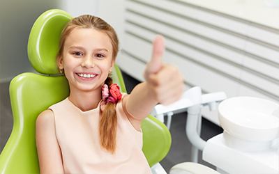 A young girl sitting in a dental chair giving a thumbs up