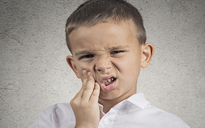 A young boy holding the side of his mouth in pain