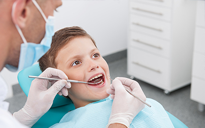 A young boy getting his teeth checked by the dentist