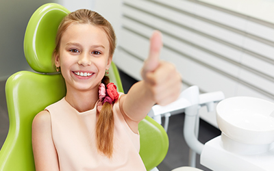 Child in dental chair with thumbs up