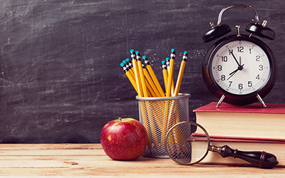 An apple, pencils, clock and books in a school setting