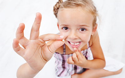 A young girl holding up a missing tooth in her hand